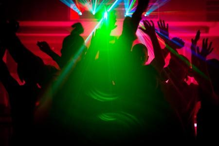 Silhouetten von tanzenden Menschen mit einer Feier in einer Diskothek, ist die Licht-Show sendet Laserstrahlen durch die beleuchtete Szene - Vorsicht: sehr psychedelische Formen und Farben