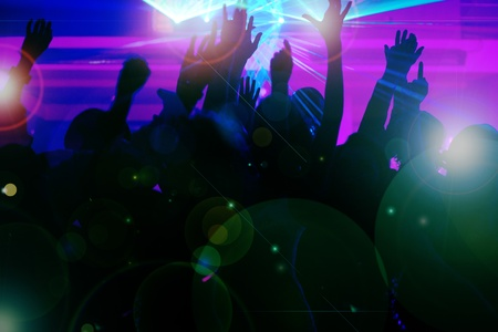 club scene: Silhouettes of dancing people having a celebration in a disco club, the light show is sending laser beams through the backlit scene - beware: very psychedelic forms and colors