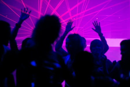Silhouetten von tanzenden Menschen mit einer Feier in einer Diskothek, ist die Licht-Show sendet Laserstrahlen durch die beleuchtete Szene