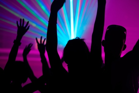 Silhouettes of dancing people having a celebration in a disco club, the light show is sending laser beams through the backlit scene Stock Photo - 10448765