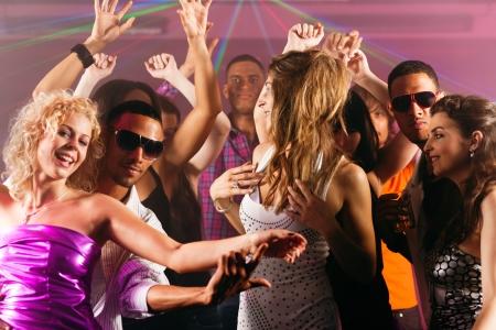 Dance actie in een discotheek - groep vrienden, mannen en vrouwen van verschillende etnische afkomst, dansen op de muziek met veel plezier