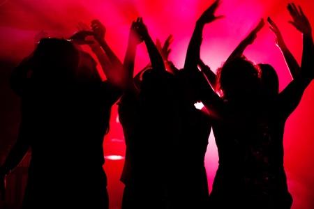 gente bailando: Siluetas de personas bailando con una fiesta en una discoteca, el espectáculo de luz está enviando rayos láser a través de la escena a contraluz