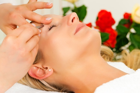 eyebrow trimming: Woman at the cosmetic salon gets the eyebrows trimmed; in the background roses