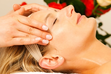 head massage: Woman enjoying a wellness head massage in a spa setting with roses in the background, she is very relaxed