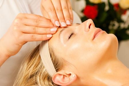 Mujer disfrutando de un masaje en la cabeza de bienestar en un ambiente de spa con rosas en el fondo, ella es muy relajada Foto de archivo