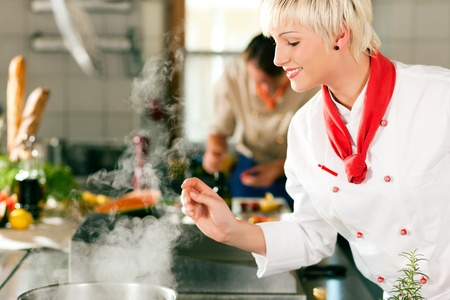 cooks: Two chefs in teamwork - man and woman - in a restaurant or hotel kitchen cooking delicious food