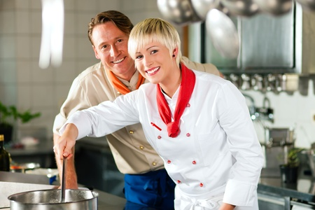 chefs: Two chefs in teamwork - man and woman - in a restaurant or hotel kitchen cooking delicious food