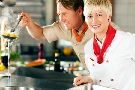Zwei K�che in Teamarbeit - ein Mann und eine Frau - in einem Restaurant oder Hotelk�che kochen leckeres Essen, so ist er unter die Nudeln