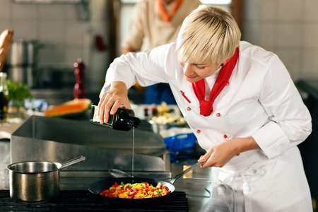 cooking oil: Two chefs in teamwork - man and woman - in a restaurant or hotel kitchen cooking delicious food, she is putting olive oil in the ratatouille