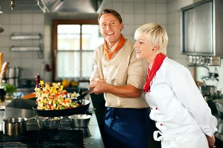 hombre cocinando: Dos cocineros en el trabajo en equipo - hombre y mujer - en la cocina del hotel o restaurante cocina deliciosa comida, �l est� trabajando en el pisto en el pan
