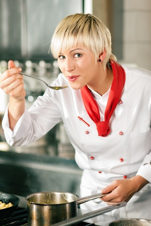 preparing: Female chefs in a restaurant or hotel kitchen cooking delicious food, tasting the half finished dish with a spoon