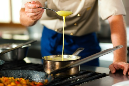 Chef - only torso to be seen - in a restaurant or hotel kitchen cooking; he is preparing the sauce photo