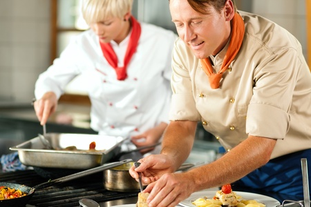Two chefs in teamwork - man and woman - in a restaurant or hotel kitchen cooking delicious food, both are finishing the dishes Stock Photo - 10448814