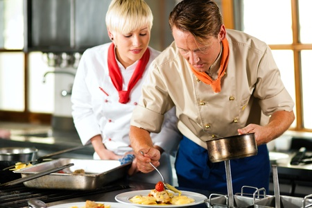Two chefs in teamwork - man and woman - in a restaurant or hotel kitchen cooking delicious food, he is decorating the dishes, she is watching photo