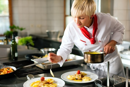 chefs: Female chef in a restaurant or hotel kitchen cooking delicious food, she is decorating the dishes Stock Photo
