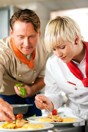 Two chefs in teamwork - man and woman - in a restaurant or hotel kitchen cooking delicious food, both are decorating the dishes  Stock Photo