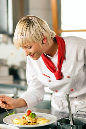 Female chefs in a restaurant or hotel kitchen cooking delicious food, tasting the half finished dish with a spoon Stock Photo - 10448827