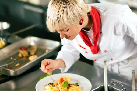 Female chefs in a restaurant or hotel kitchen cooking delicious food, tasting the half finished dish with a spoon  photo