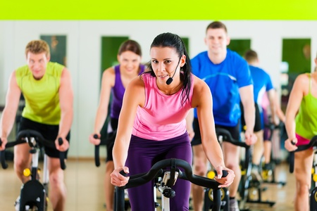 fitness instructor: Group of five people - men and women - spinning in gym or fitness club exercising their legs doing cardio training; the trainer is in front