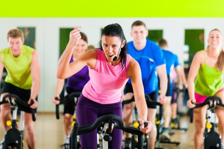 Group of five people - men and women - spinning in gym or fitness club exercising their legs doing cardio training; the trainer is in front