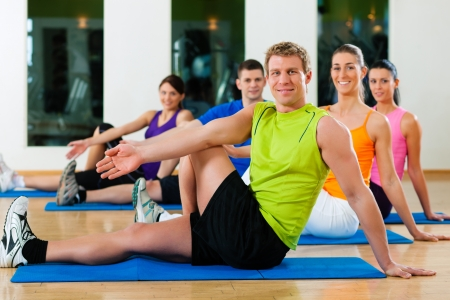 Group of five people is doing stretching exercises in fitness club on gym mats photo