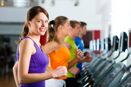 sports: Running on treadmill in gym or fitness club - group of women and men exercising to gain more fitness