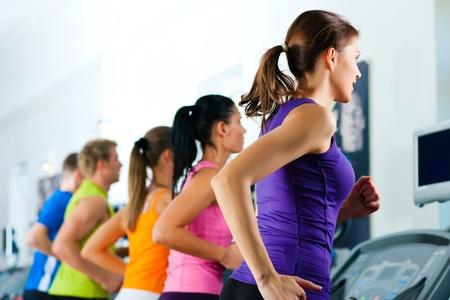 hacer footing: Correr en la cinta en el gimnasio o club de fitness - grupo de mujeres y hombres que ejercen para obtener m�s aptitud