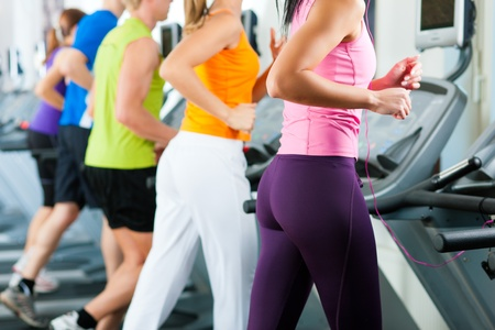 Running on treadmill in gym or fitness club - group of women and men exercising to gain more fitness Stock Photo - 10448848