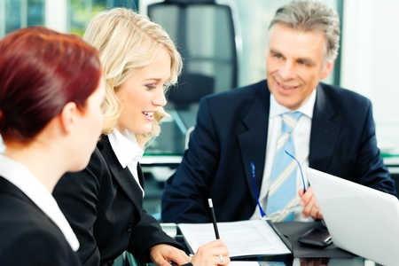 business advice: Business - meeting in an office; the businesspeople are discussing a document