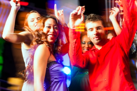 asian american: Group of party people - men and women - dancing in a disco club to the music