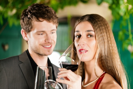 Couple at winetasting with red wine in a restaurant photo