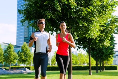 life balance: Urban sports - couple jogging for fitness in the city on a beautiful summer day Stock Photo