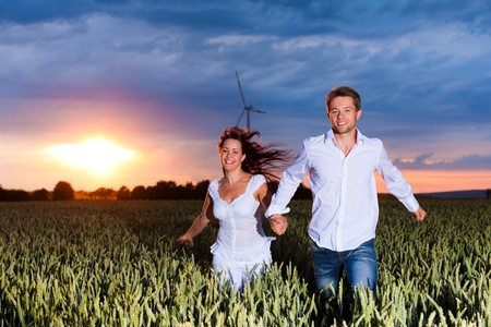 Happy couple is running over grainfield at night; a storm is coming photo