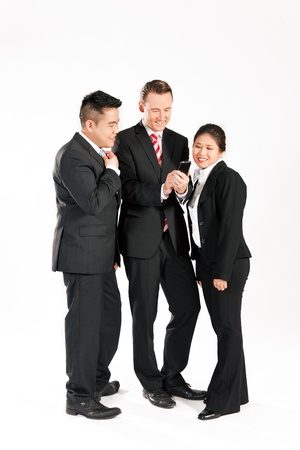 Multi-ethnic business people standing together and looking at a mobile phone photo
