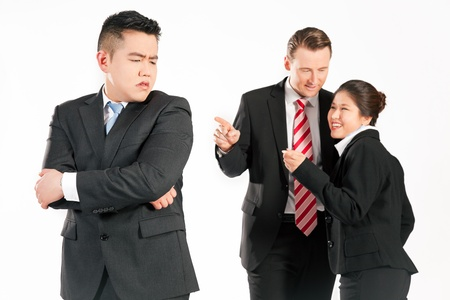 exclude: Business people (multi-ethnic) pointing their fingers on a colleague - mobbing
