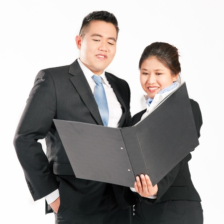 work experience: Asian business people studying a folder – the business is running well