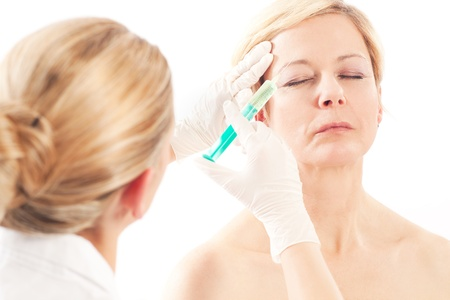 Botox - Age and beauty; a doctor is doing the injection photo