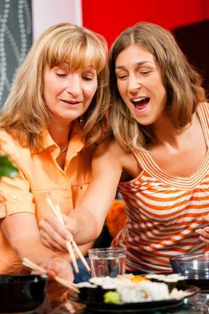 Mother and adult daughter eating sushi at home photo