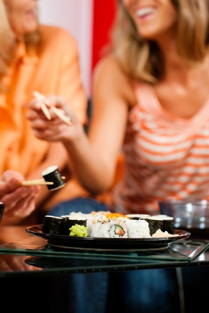 sushi plate: Mother and adult daughter eating sushi at home - FOCUS is on the sushi plate