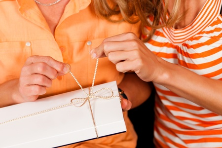 trustful: Two women – mother and daughter – sitting on a couch; the daughter has given her mother a gift