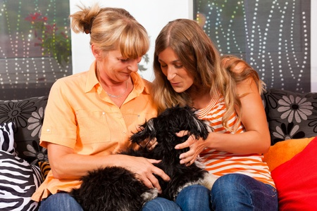 Two women – presumably mother and daughter – playing with a dog in her home photo