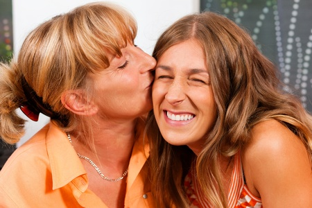 Mother is kissing her daughter as a sign of love photo