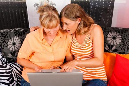 demografia: Hija internet explicando a su madre en el hogar, las mujeres están sentados delante de un PC portátil