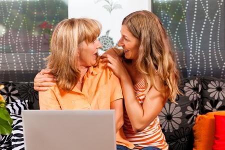 demografia: Hija internet explicando a su madre en el hogar, las mujeres est�n sentados delante de un PC port�til