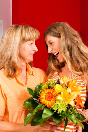 thankful: Mother and daughter – the daughter has given her mother flowers    Stock Photo
