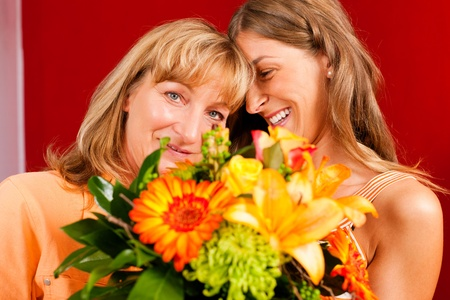 grown ups: Mother and daughter – the daughter has given her mother flowers    Stock Photo
