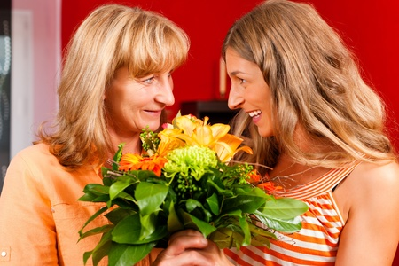 trustful: Mother and daughter – the daughter has given her mother flowers    Stock Photo