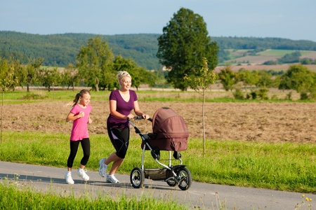 joggers: Family sport - mother and daughter jogging down a path with a baby stroller at a wonderful sunny day