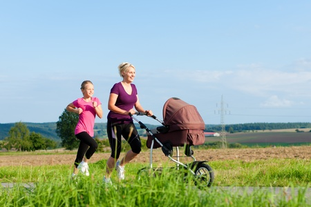 buggy: Family sport - mother and daughter jogging down a path with a baby stroller at a wonderful sunny day