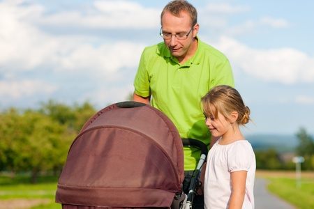 Father with child and a baby lying in a baby buggy walking down a path outdoors photo